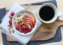 A portion of porridge with apples and a black coffee.