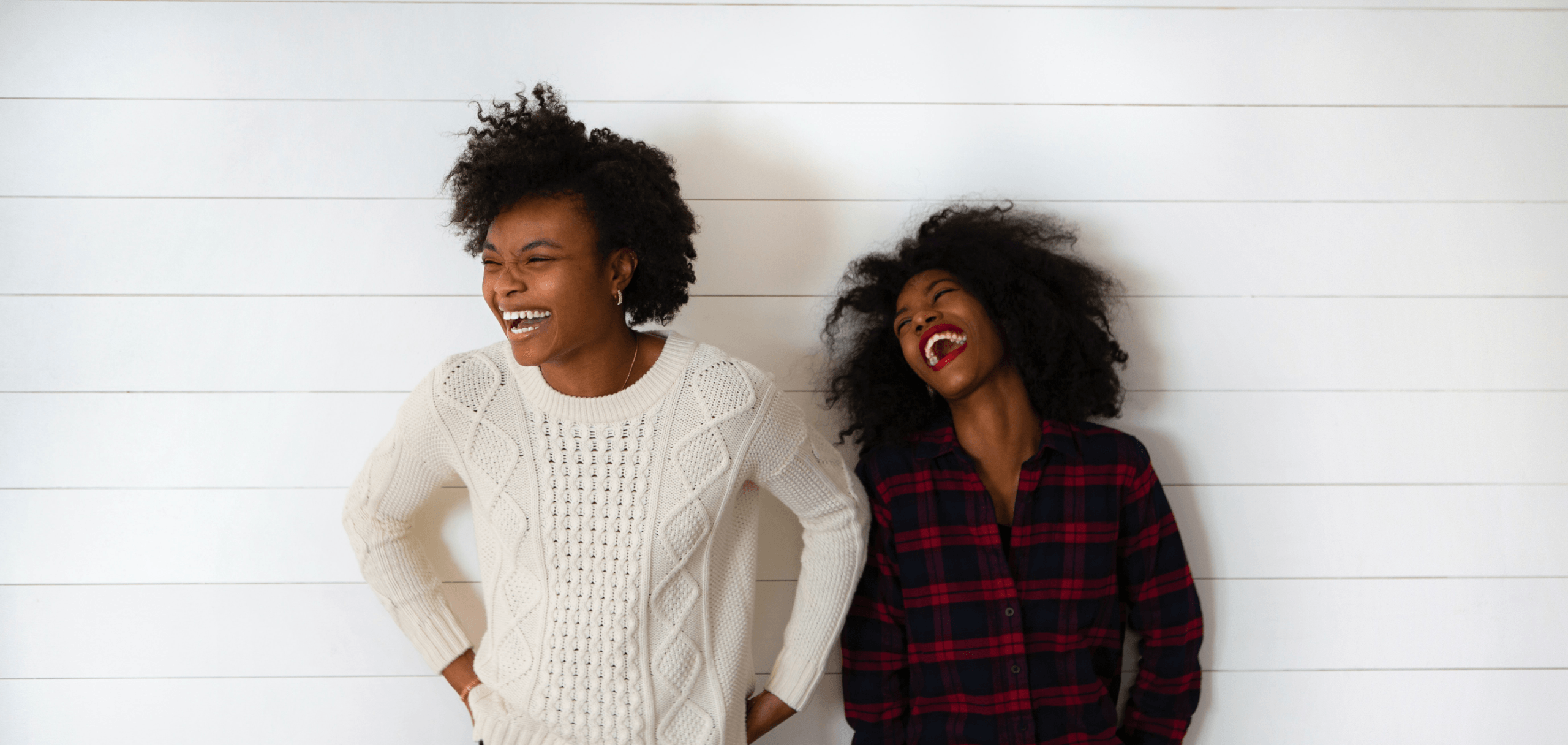 Two females laughing against a white wooden backdrop.