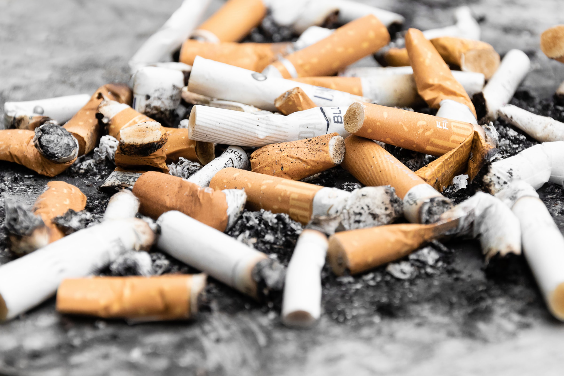 Pile of stubbed out cigarettes in ash.