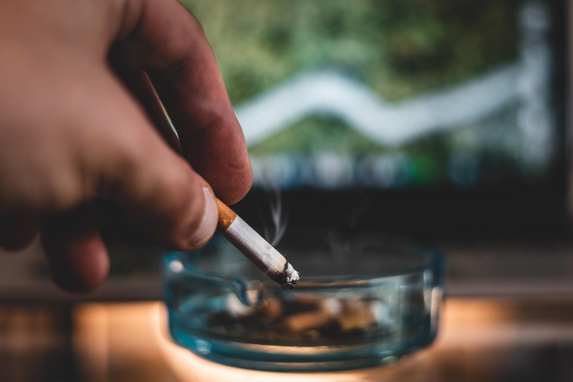 A person tabbing cigarette ash into a glass ashtray.