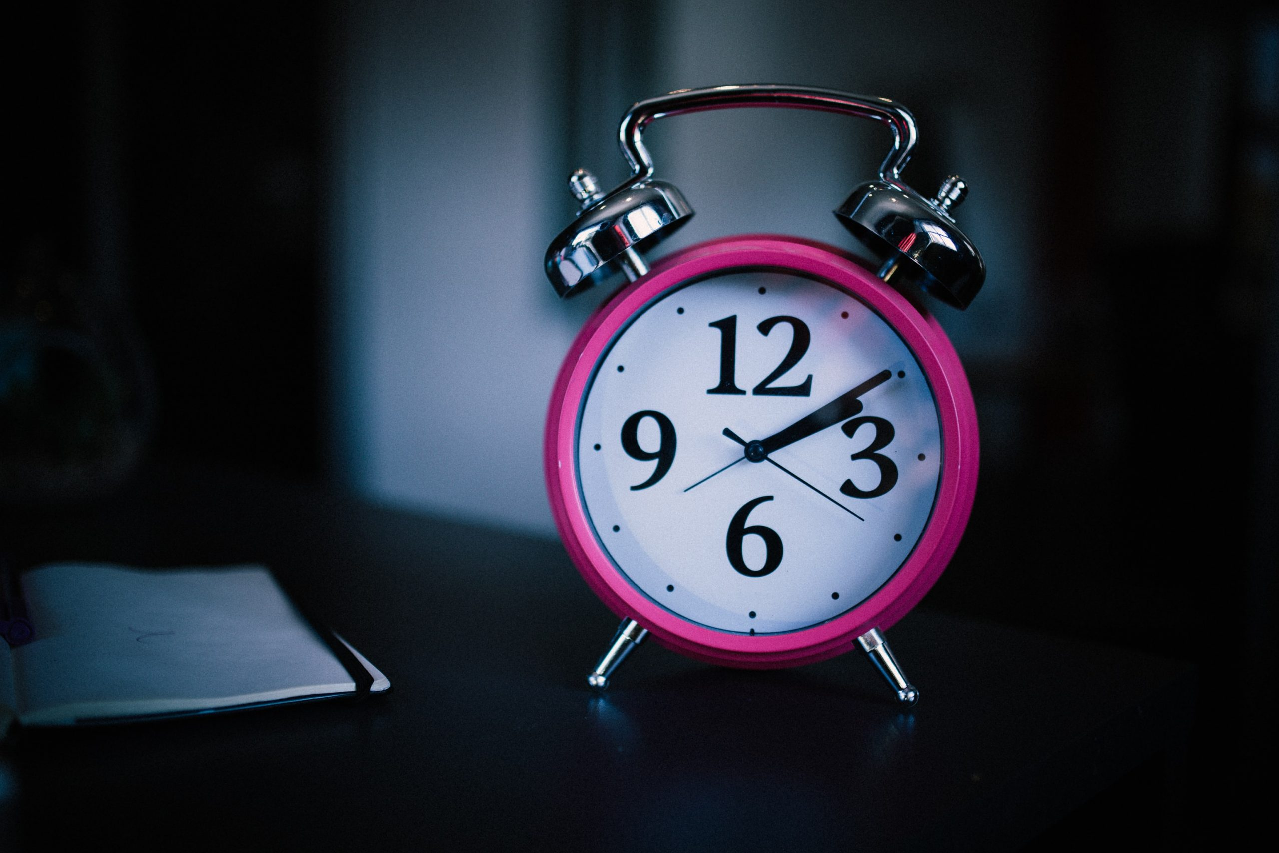 A close up photograph of a traditional pink analogue alarm clock.