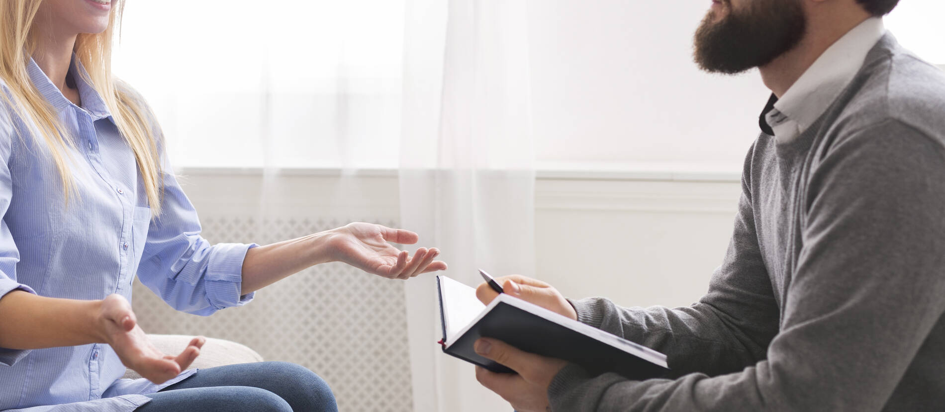 Psychotherapist talking to patient at office, panorama.