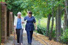 A care worker walking alongside an elderly lady in the park.